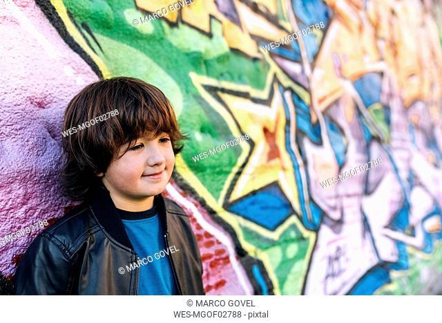 Portrait of little boy standing in front of graffiti wall