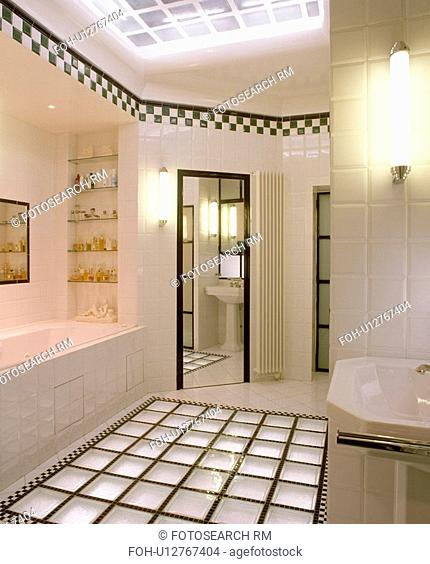 Glass brick flooring in modern white tiled bathroom with black+white chequerboard tiling border below ceiling&13,&10