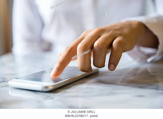Finger of African American woman using cell phone