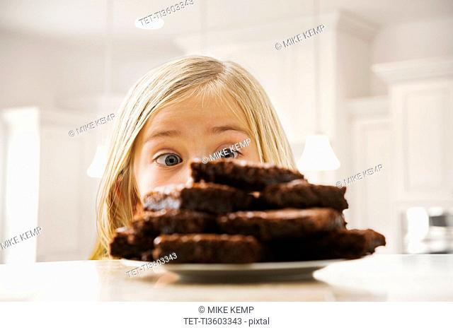 Girl (6-7) looking at heap of brownies
