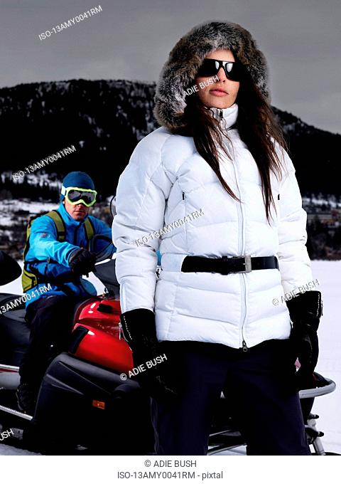 Lady posing in front of man on skidoo