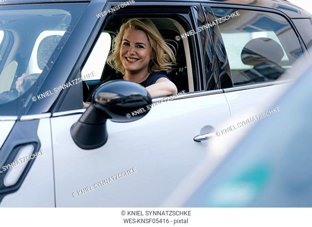 Portrait of smiling woman looking out of car window