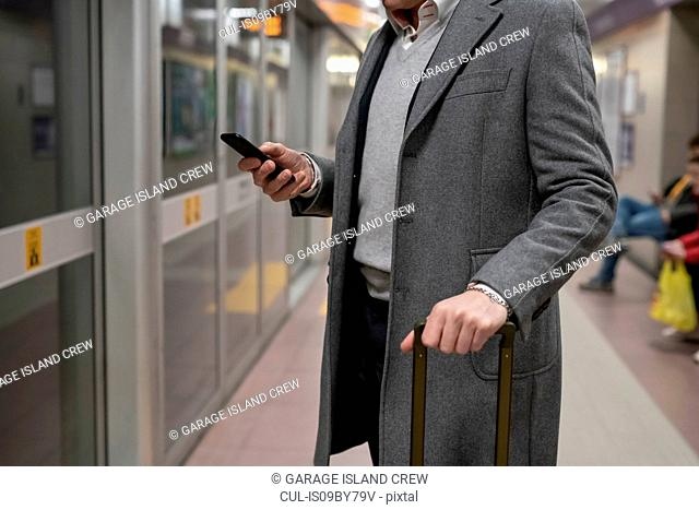 Businessman using smartphone on train platform