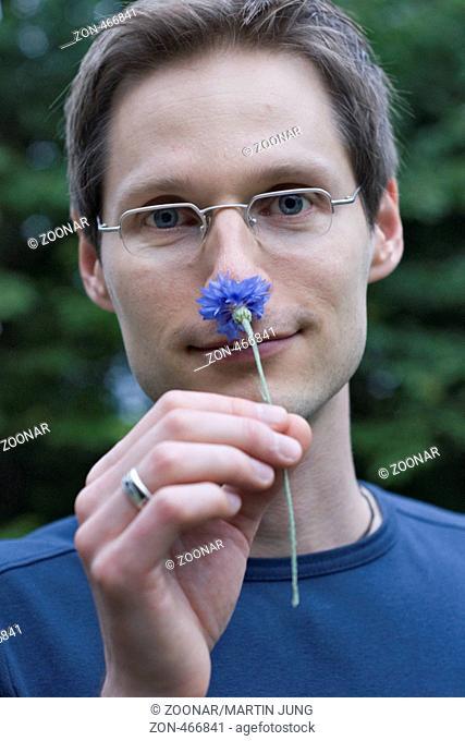 Ein Mann riecht an einer Kornblume A man smelling a cornflower