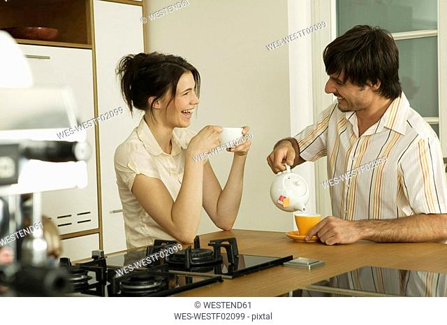 Young couple in kitchen, drinking tea, smiling