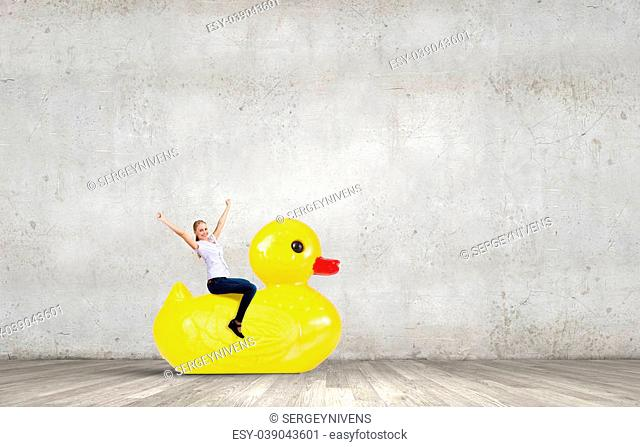 Young happy businesswoman riding yellow rubber duck