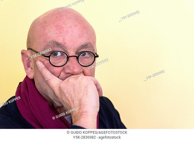Tilburg, Netherlands. Portrait of bald, mature adult man wearing glasses, leaning in one hand against a yellow background