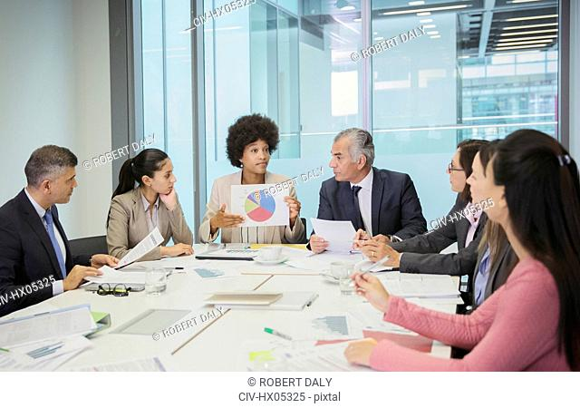 Businesswoman with pie chart leading conference room meeting