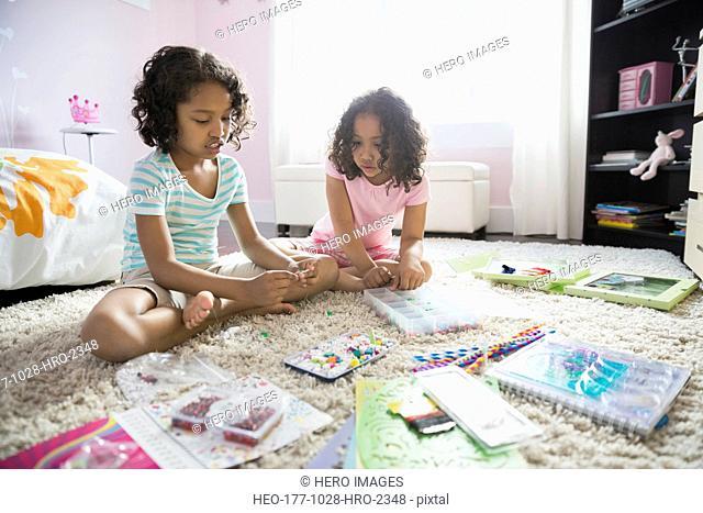 Little girls doing crafts in bedroom