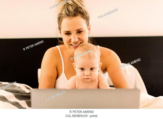Baby girl and mother sitting up in bed staring at laptop