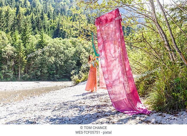 Woman hanging up colourful cloths at the riverside