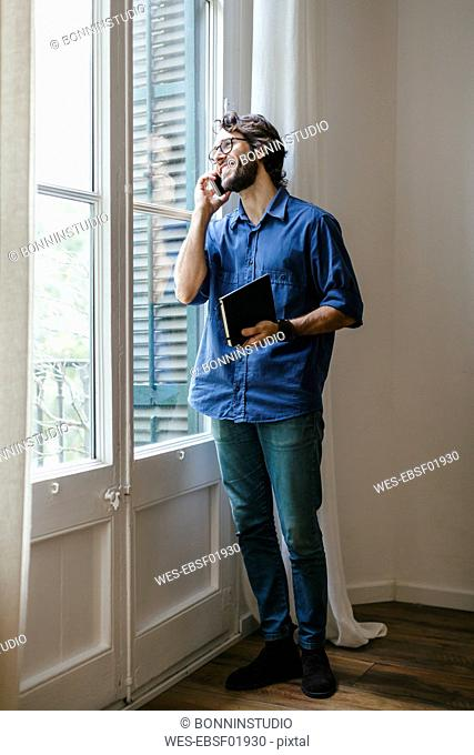 Businessman standing at office window, using smart phone