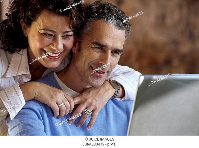 Middle-aged couple using laptop at home