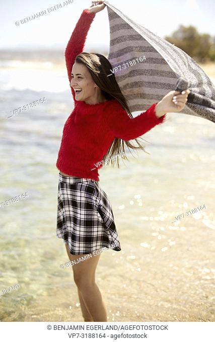 Young woman at the beach with towel. Crete, Greece