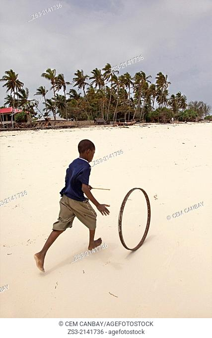 Child playing with an old bicycle wheel on the beach of Nungwi, Zanzibar, Tanzania, East Africa
