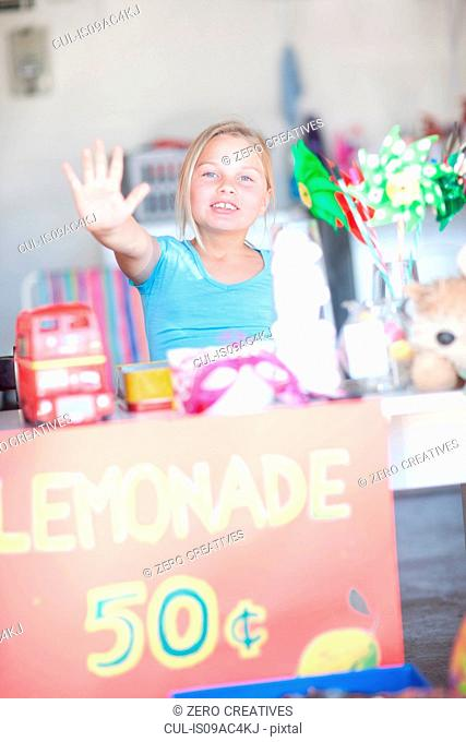 Young girl behind stall with her hand up