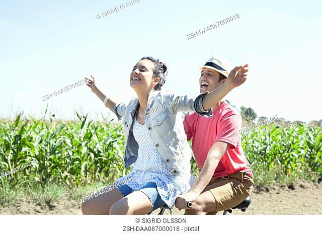 Couple riding bike together, woman with arms outstretched