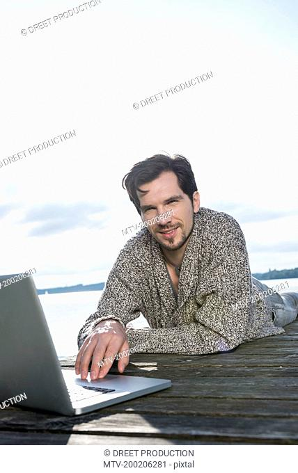 Portrait man lying on wooden jetty using laptop
