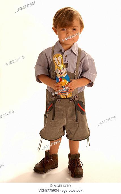 Ein kleiner Junge in Lederhose mit Schokoladen-Osterhasen im Arm, 2006 - Germany, 01/03/2006