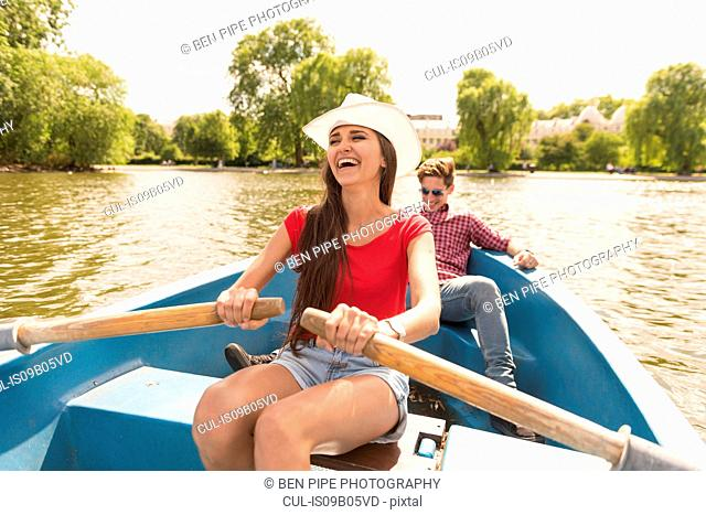 Happy young couple rowing a boat in Regents Park, London, UK