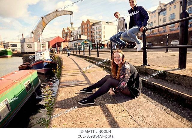 Portrait of three friends sitting beside river, Bristol, UK