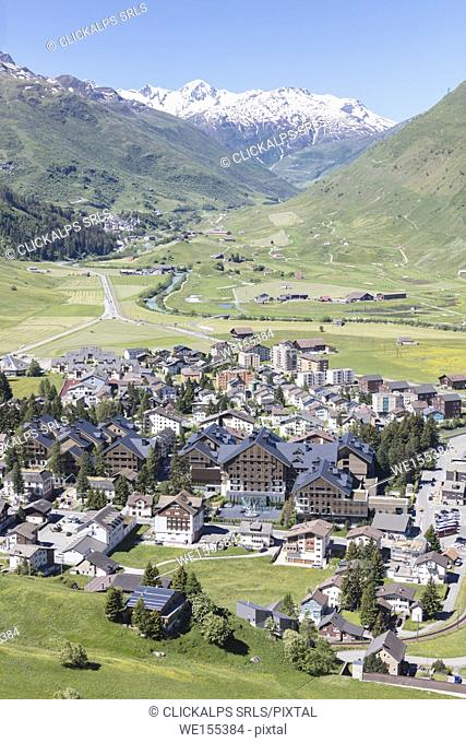 The alpine village of Andermatt surrounded by green meadows and snowy peaks in the background Canton of Uri Switzerland Europe