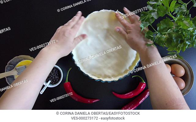 Woman hands press the edges of a savory pie with their fingers to close them, then brush the surface with egg yolk