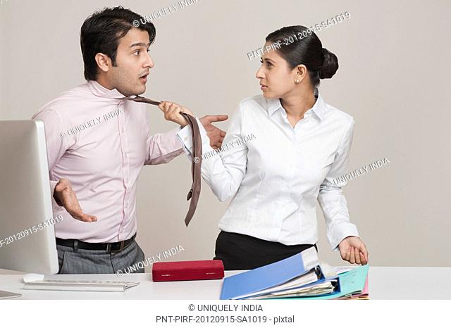 Businesswoman pulling necktie of a businessman in an office