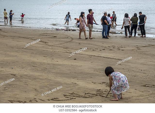 Girl draws pictures on the beach, Telok Melano , Sematan, Sarawak, Malaysia