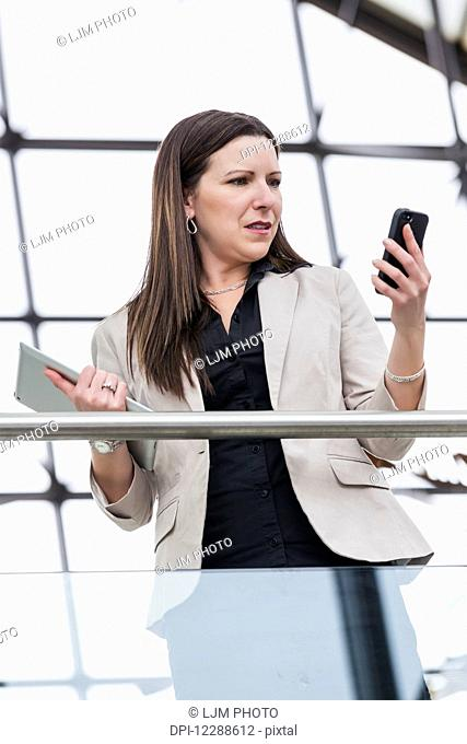 Mature business woman shocked at message received on her smart phone; Edmonton, Alberta, Canada