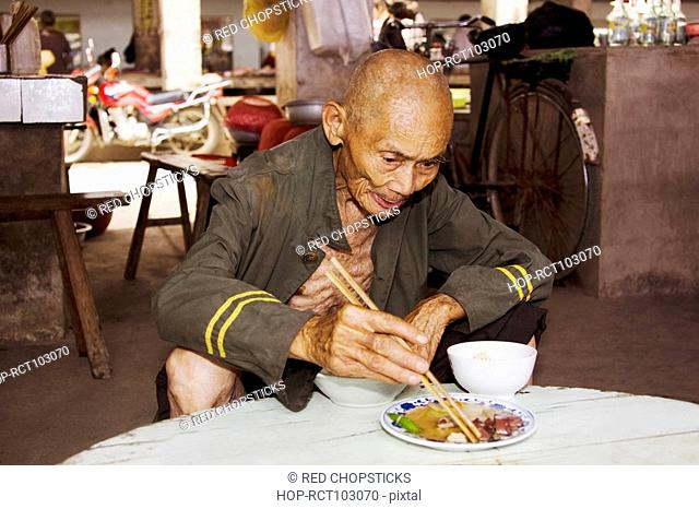Senior man eating food in a restaurant, Xingping, Yangshuo, Guangxi Province, China