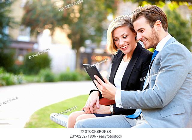 Business Couple Using Digital Tablet On Park Bench
