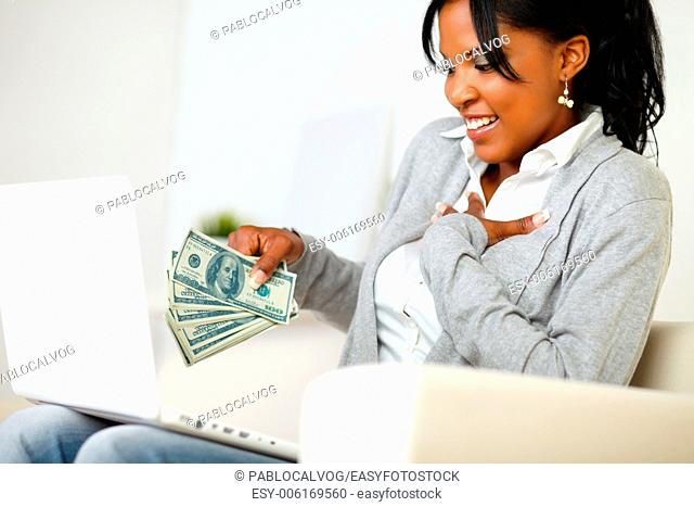 Portrait of an excited ambitious young woman with money while is sitting on sofa at home in front a laptop