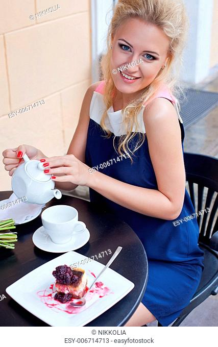a beautiful young blond girl with blue eyes in summer dress at the table in pavement cafe is going to pour tea into the cup
