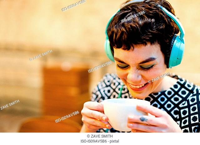 Mid adult woman, wearing headphones, holding coffee cup, smiling