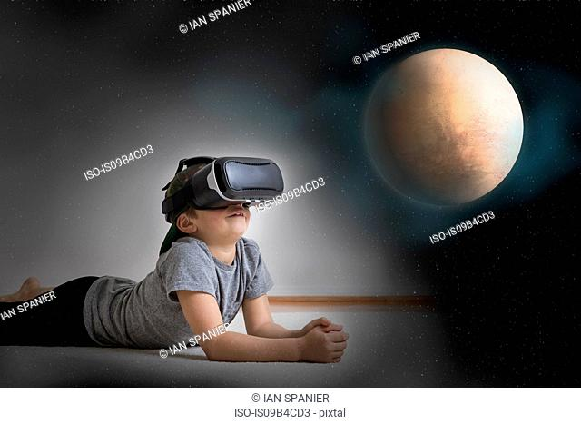 Young boy lying on floor, wearing virtual reality headset, looking at planet, digital composite