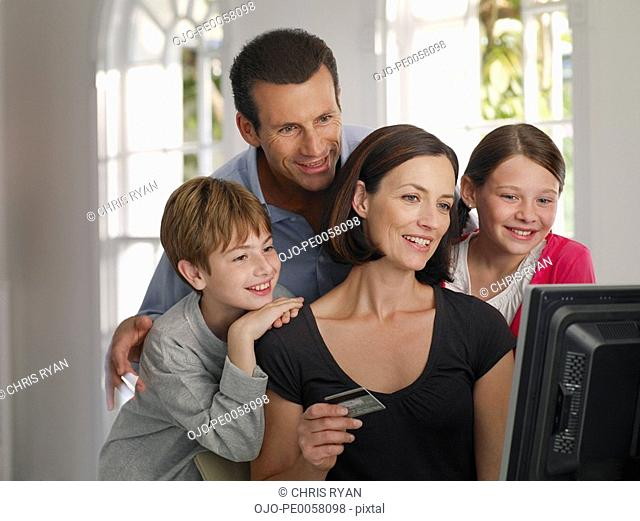 Couple and young boy and girl with credit card shopping online