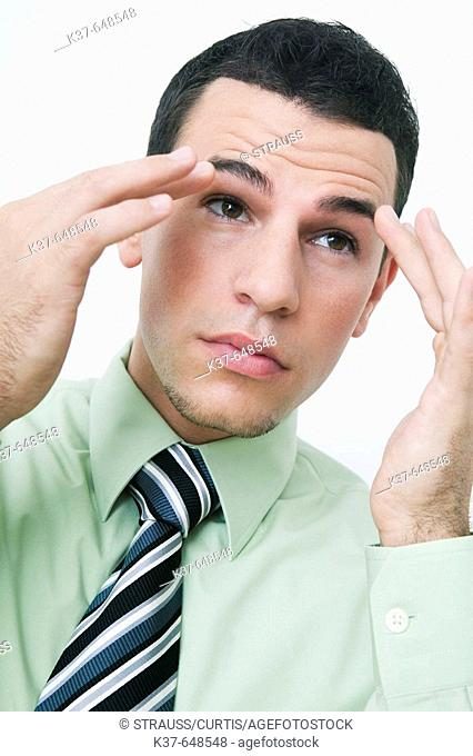Man smoothing his eyebrows & checking himself in mirror after tying his tie & before going to work