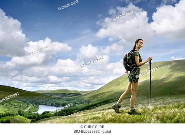 Caucasian woman hiking on green hill