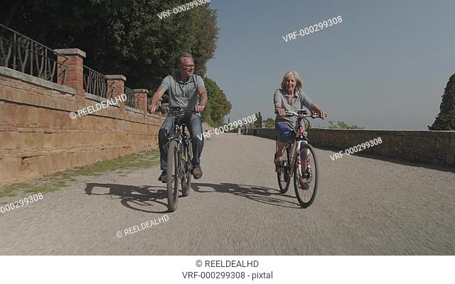 Senior couple cycling on electric bicycles