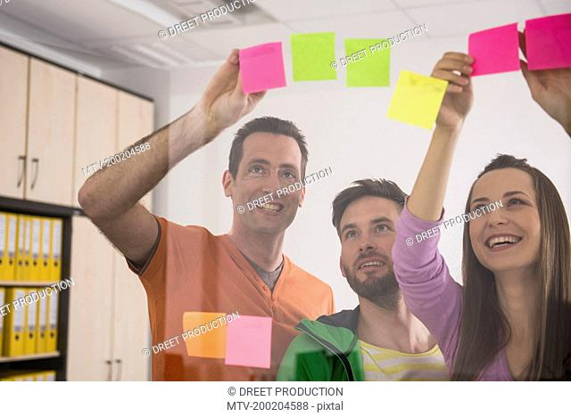 Work colleagues planning playing using post-its