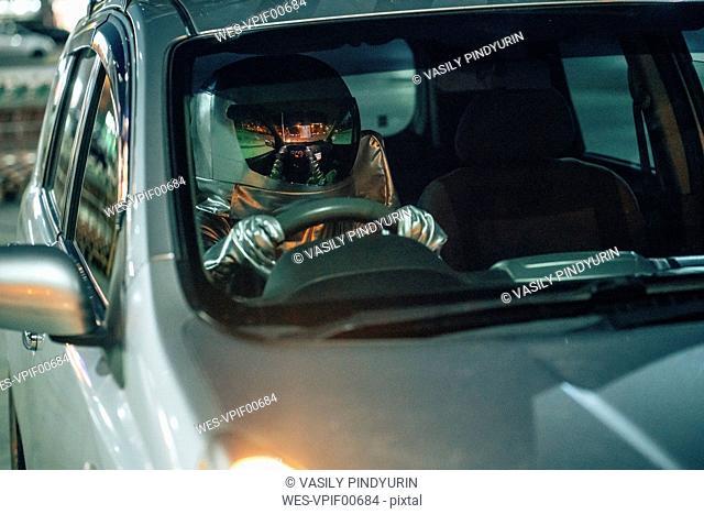 Spaceman driving car at night