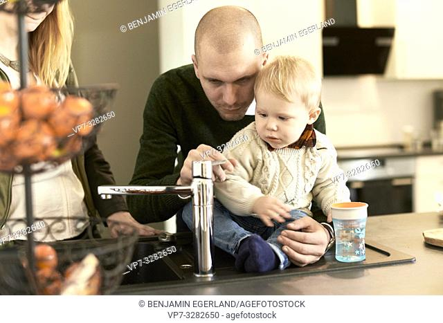 parents with baby toddler child next to water faucet in kitchen at home, in Cottbus, Brandenburg, Germany