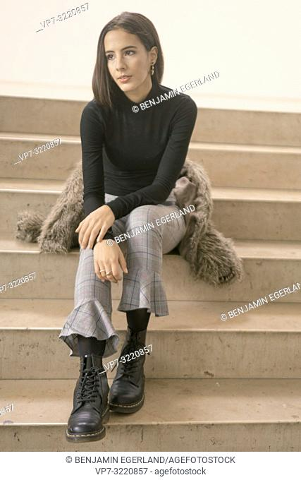 young woman sitting on stairs indoors, pensive mood, in Munich, Germany