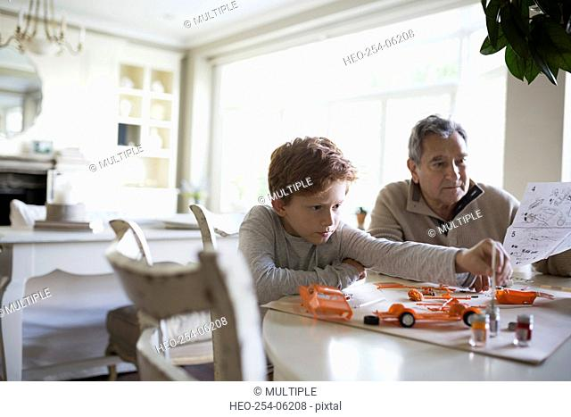 Grandfather and grandson assembling model cars
