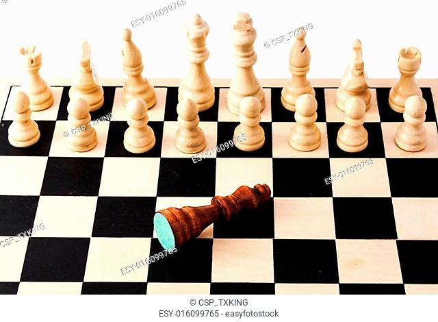 High angle shot of an chess board with a fallen king in front of a full row of chess pieces