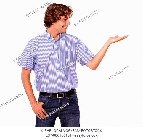 Portrait of a fashionable young male in jeans with palm out for copyspace on white background