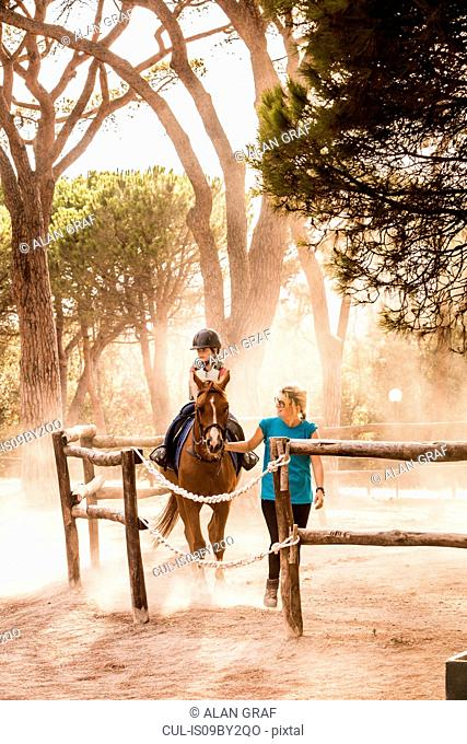 Mother leading horse riding daughter in paddock, Portoferraio, Tuscany, Italy