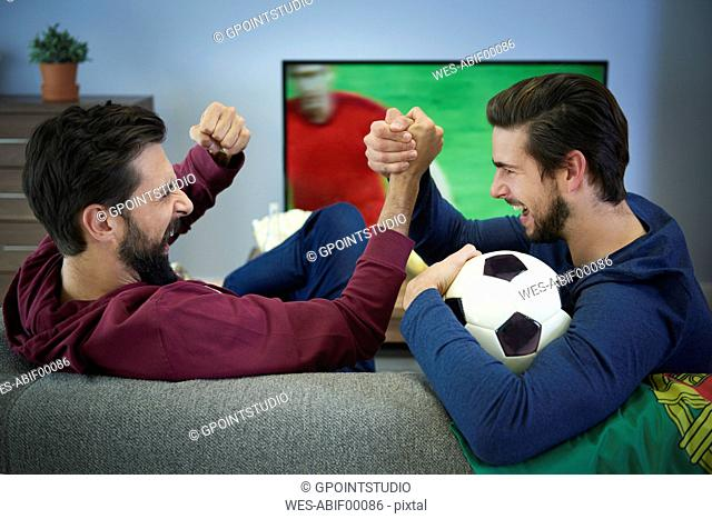 Two football fans watching Tv and cheering
