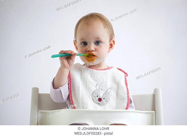 Portrait of baby girl on high chair eating mush